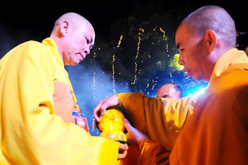 Trưởng ban tổ chức đón nhận ánh sáng từ bàn thờ Phật