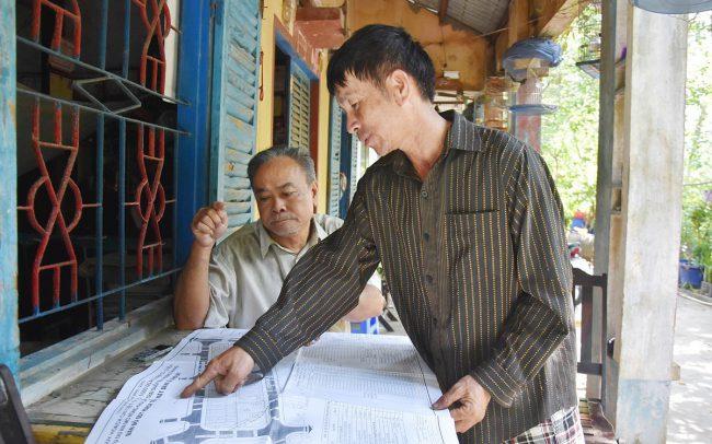 """Ông Trần Văn Giêng (ngồi) bên căn nhà dột nát vì vướng dự án """"treo"""""""